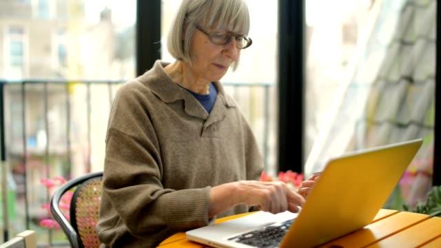 Senior adult woman shopping on internet video