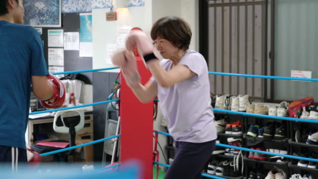 vidéos et rushes de formation de boxercise senior femmes adultes avec l'entraîneur mid-adult - seulement des japonais