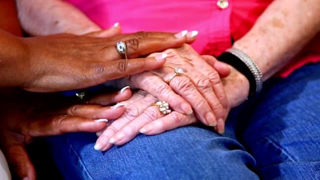 Senior adult women comfort each other, holding hands. video