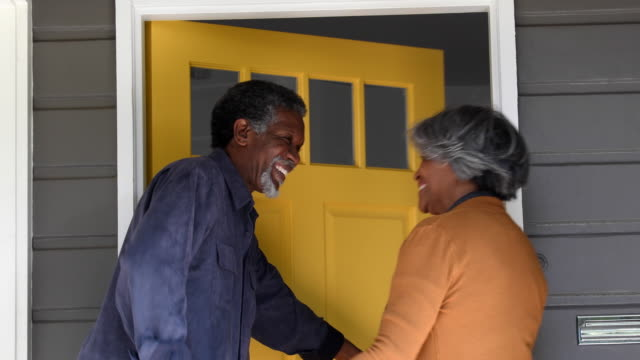 Senior African American couple arriving home, opening front door video