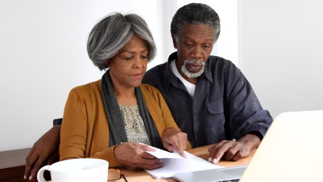 vídeos y material grabado en eventos de stock de pareja senior afroamericano discutir finanzas inicio - trabajo de oficina