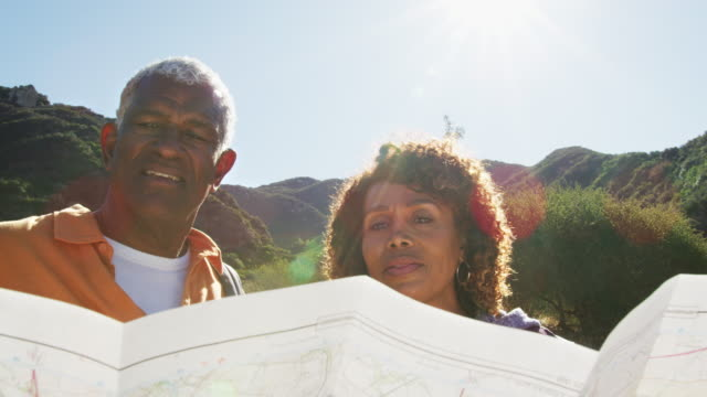 Senior African American Couple Looking At Map As They Hike Along Trail In Countryside Together