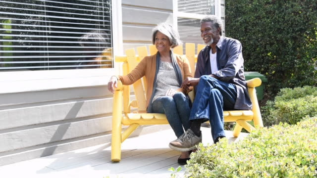Senior African American couple on bench, looking away video