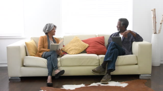 senior african american couple on sofa, man showing tablet - 60 69 anni video stock e b–roll