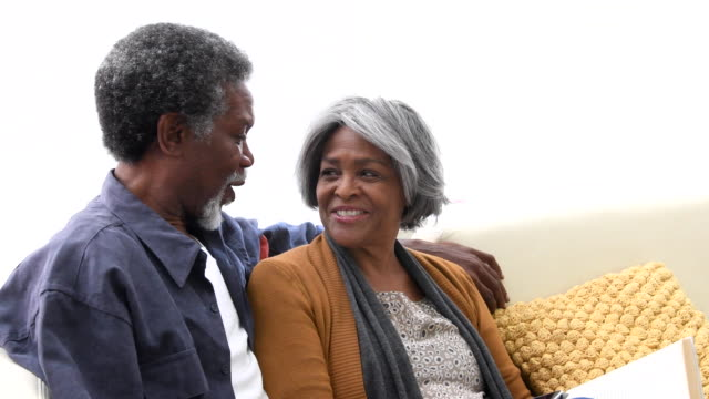 Senior African American couple on sofa smiling and laughing video