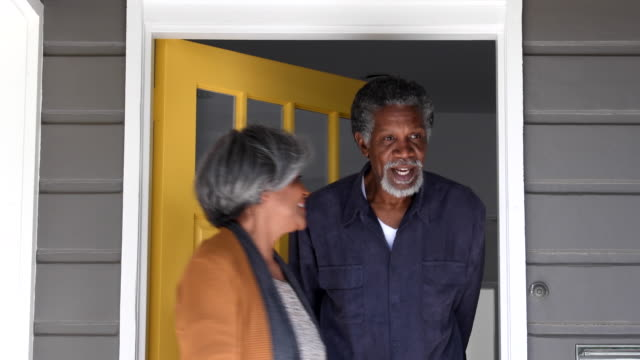 Senior African American couple opening door and leaving house
