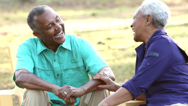 Senior African American couple sitting outdoors, talking video