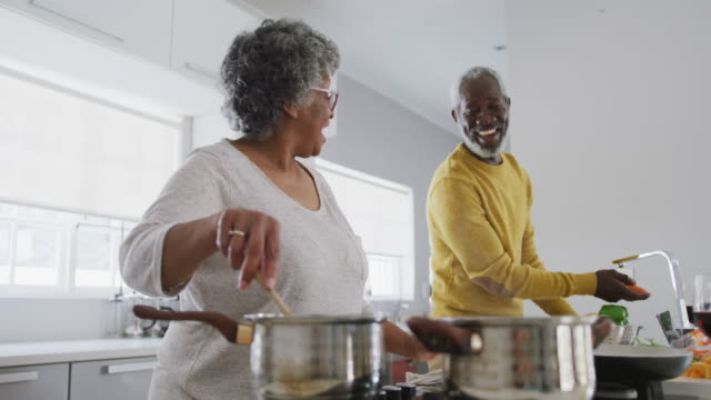 Video A senior african american couple spending time together at home and cooking social distancing in qua