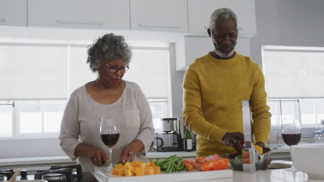 A senior african american couple spending time together at home and cooking social distancing in qua
