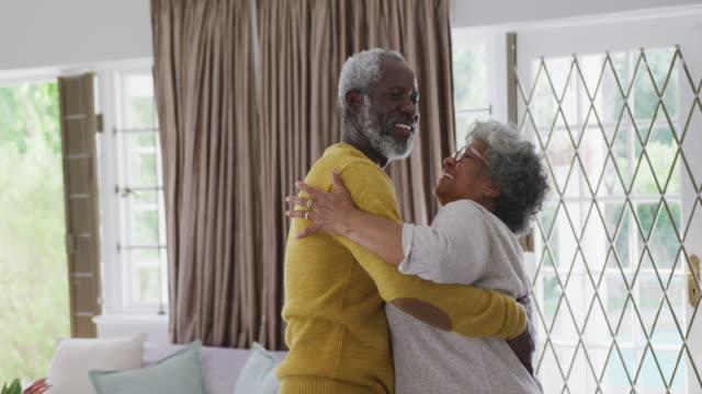 una coppia afro-americana anziana che trascorre del tempo insieme a casa ballando nel salotto social di - anziani attivi video stock e b–roll