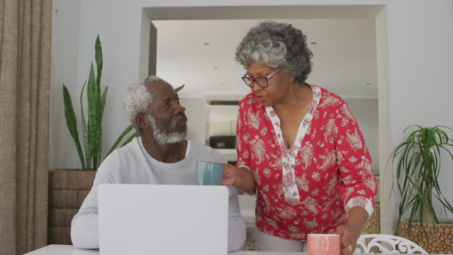 A senior african american couple spending time together at home using a laptop. social distancing in