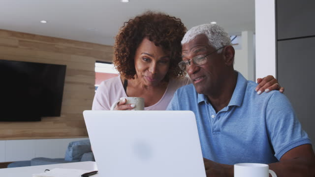 senior african american couple using laptop to check finances at home - coppia anziana video stock e b–roll