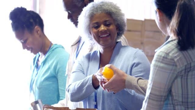 vídeos y material grabado en eventos de stock de banco de alimentos de afroamericanos senior voluntario recibe alimentos donados - food drive