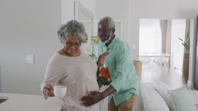 A senior African American man offering flowers to his wife