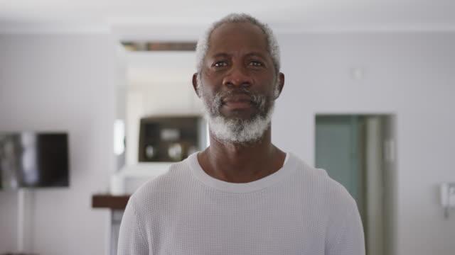старший афроамериканец улыбается в камеру. социальное дистанцирование в карантине. - зрелый возраст стоковые видео и кадры b-roll
