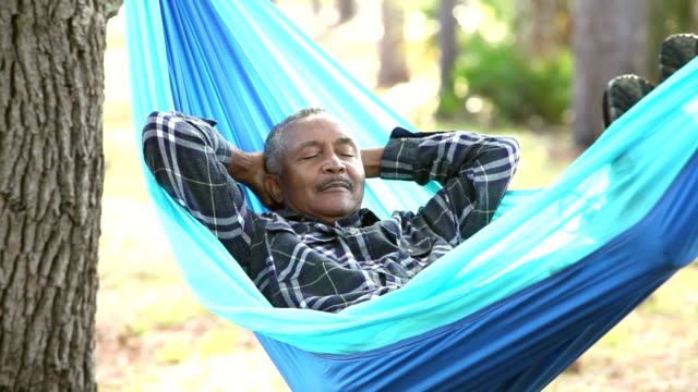 Senior African American man taking nap in hammock video