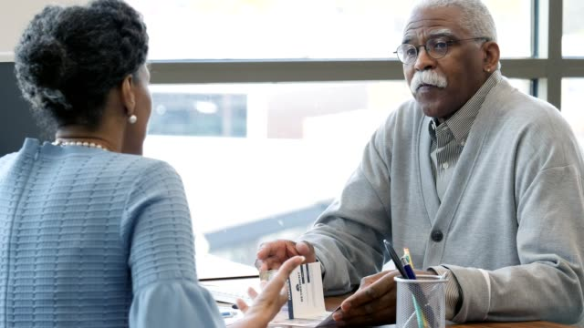 Senior African American man talks with bank manager Female bank account manager greets a senior male customer with a handshake. The man asks the manager question while looking at an informational flyer. loan stock videos & royalty-free footage