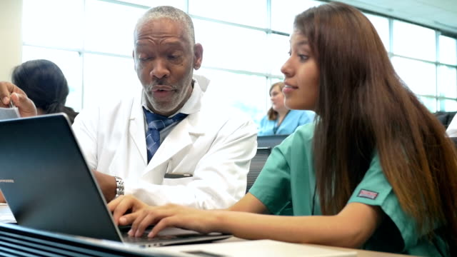 Senior African American professor tutoring nursing or medical student in class video