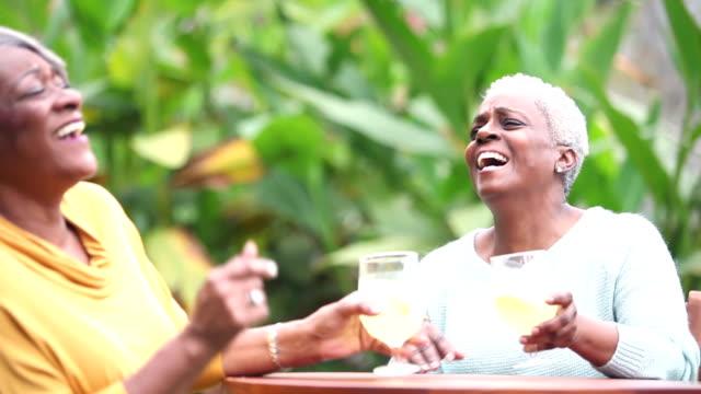 vídeos de stock e filmes b-roll de senior african american woman conversing, drinking - limonada tradicional