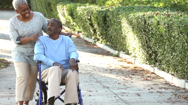 Senior African American woman pushing man in wheelchair A senior African American couple out for a walk in the park. The man is sitting in a wheelchair and his wife is pushing him. They are talking and laughing. He reaching up and she takes his hand. sociology stock videos & royalty-free footage