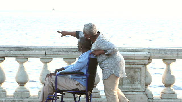 Senior African American woman pushing man in wheelchair A senior African American couple out for a walk on the waterfront. The man is sitting in a wheelchair and his wife is pushing him. They are looking at the view. They stop and the woman points out at something on the water. Then they continue on and exit. pushing wheelchair stock videos & royalty-free footage