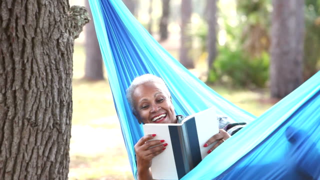 senior african american woman reading in hammock - amaca video stock e b–roll