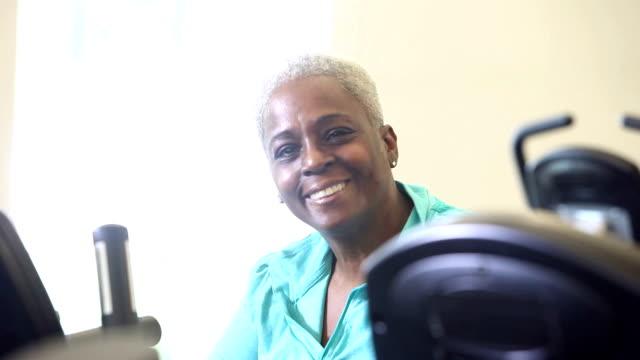 vídeos y material grabado en eventos de stock de mujer senior african american hacer ejercicio en gimnasio en bicicleta - estilo de vida austero