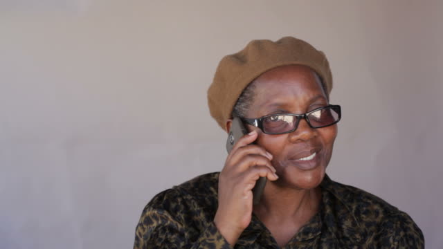 Senior african woman talking to a friend on her cellphone video