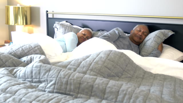 Senior African-American couple asleep in bed A senior African-American couple in their 60s sleeping side by side in bed. They are both asleep lying on their sides. The man rolls over to his other side. It is morning, almost time to wake up. covering stock videos & royalty-free footage