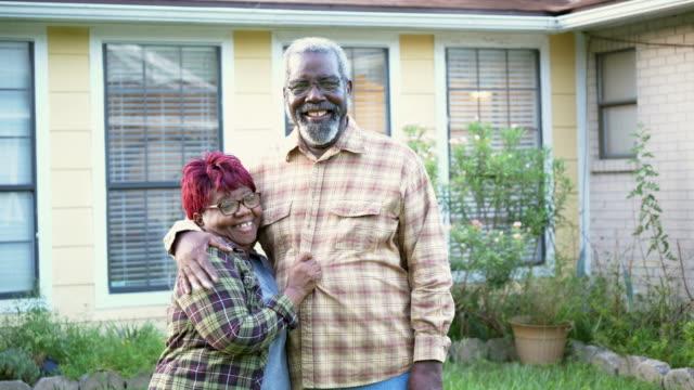 coppia afro-americana senior che si abbraccia davanti a casa - bassino video stock e b–roll