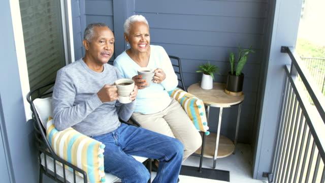 vidéos et rushes de couples afro-américains principaux détendant sur le porche - man drinking terrace