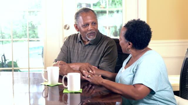 senior african-american couple talking, having coffee - 60 69 anni video stock e b–roll