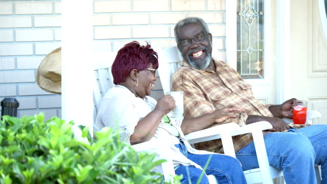 Senior African-American couple together on front porch A senior African-American couple sitting side by side on rocking chairs, drinking refreshments on their front porch. They are smiling, talking, relaxed, enjoying each other's company.  They are in their 70s. rocking chair stock videos & royalty-free footage