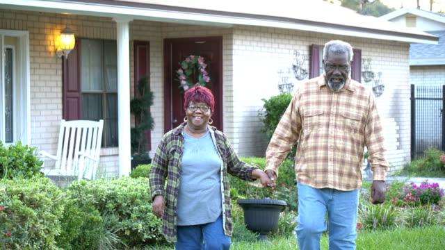 coppia afro-americana anziana che cammina davanti a casa - bassino video stock e b–roll