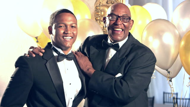 Senior African-American man and grandson wearing tuxedos video