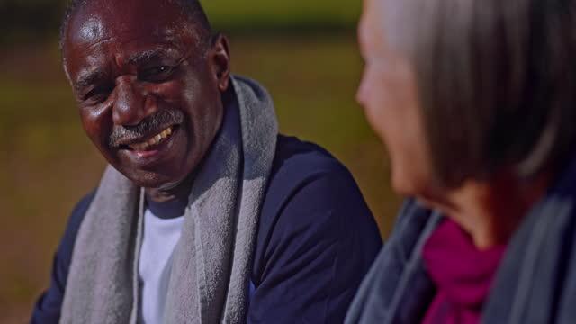 senior afro-amerikansk man vilar med vänner på bänken efter träning - black woman towel workout bildbanksvideor och videomaterial från bakom kulisserna