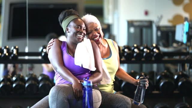 senior afro-amerikansk kvinna och ung vän på gym - black woman towel workout bildbanksvideor och videomaterial från bakom kulisserna