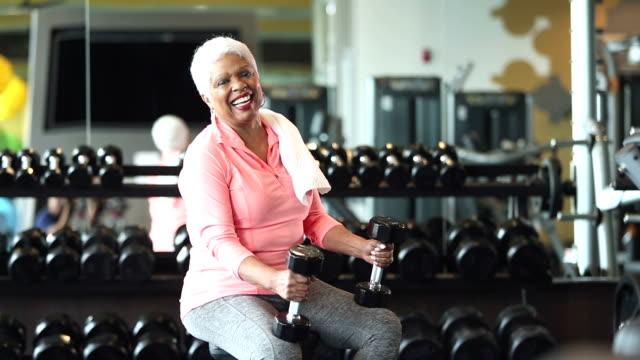 senior afro-amerikansk kvinna på gym, holding hantlar - gym skratt bildbanksvideor och videomaterial från bakom kulisserna
