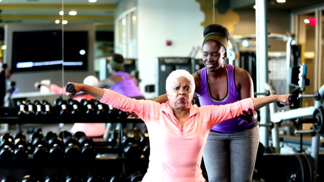 Senior African-American woman at gym, personal trainer A senior African-American woman in her 60s working out the gym, strengthening her upper body, lifting dumbbells in her hands. Her personal trainer, a young woman in her 20s, is helping her. prop stock videos & royalty-free footage