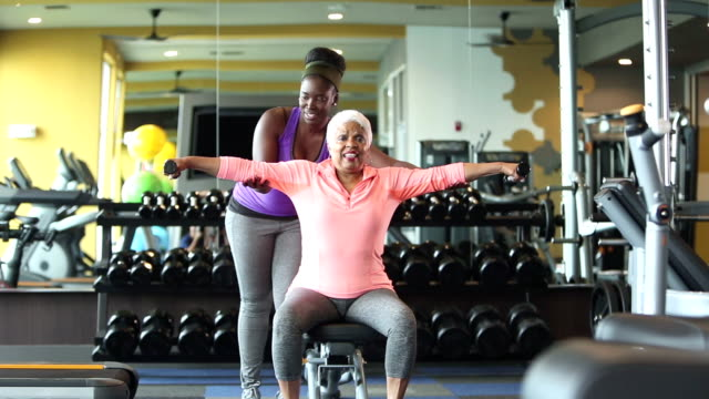 senior african-american frau im fitnessstudio, personal trainer - aktiver senior stock-videos und b-roll-filmmaterial