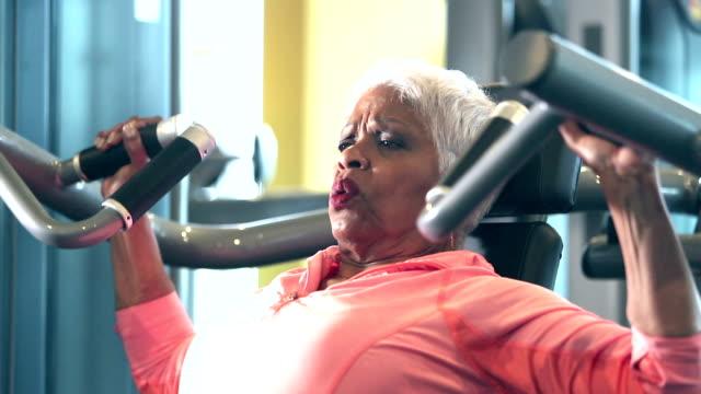 vídeos y material grabado en eventos de stock de mujer afroamericana senior en el gimnasio - entrenamiento con pesas