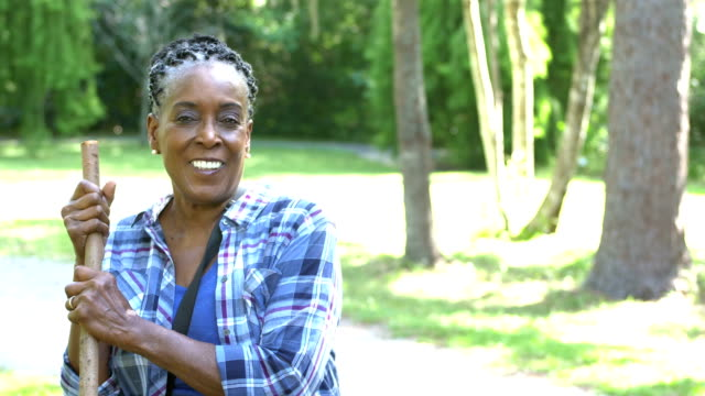 senior african-american woman hiking in the woods - woman portrait forest video stock e b–roll