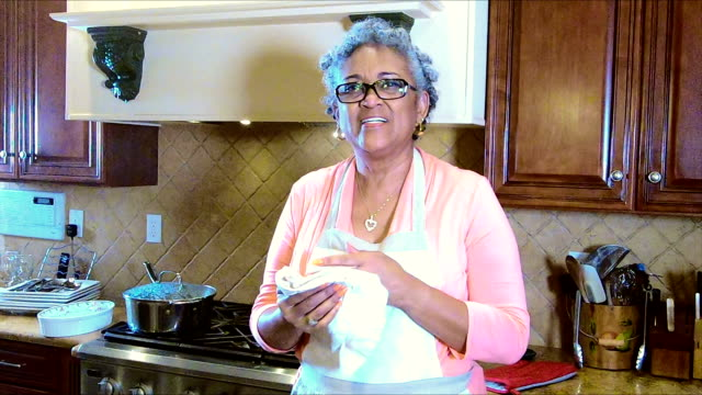 Senior African-American woman in kitchen drying hands video