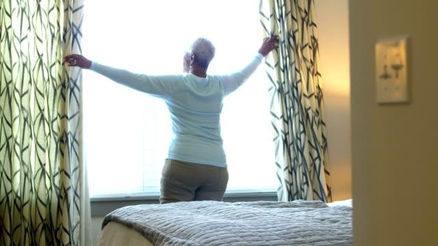 vídeos de stock e filmes b-roll de senior african-american woman lets in sunlight, new day - open window