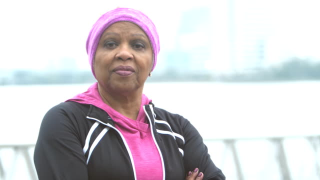 Senior African-American woman looking into the camera A serious, confident, senior African-American woman in her 60s staring at the camera, nodding her head in agreement, standing on a city waterfront with her arms crossed. real people stock videos & royalty-free footage