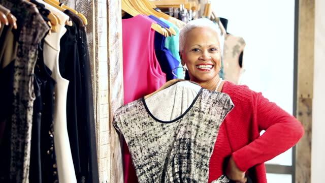 vídeos de stock, filmes e b-roll de senior afro-americana de compras para vestuário - boutique