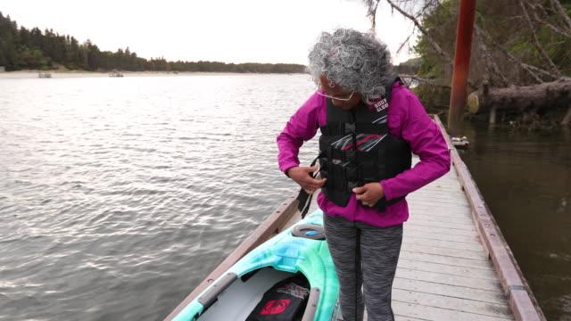 Senior age woman putting on lifejacket video
