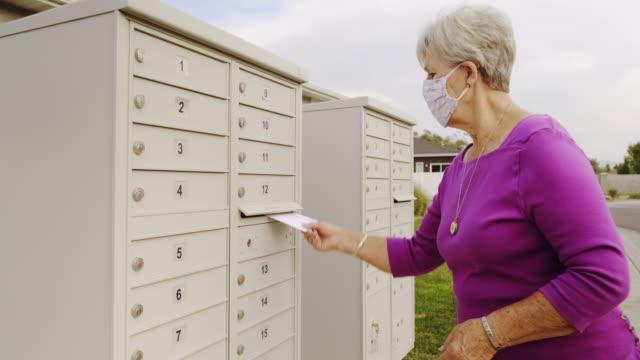 vídeos y material grabado en eventos de stock de senior age woman voting by mail - polling place