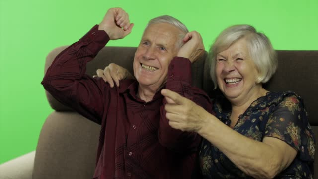 senior aged man and woman sitting together on a sofa and watching tv. chroma key - capelli grigi video stock e b–roll