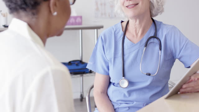 Senior Aged Nurse Helping Her Senior Aged Female Patient A senior female caucasian nurse is going through a checkup with her female patient. The patient is an ethnic senior female. nutritionist stock videos & royalty-free footage